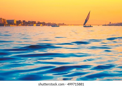 Silhouette of felucca at golden sunset, travel on sail vessel on the Nile - romantic cruise and adventure in Egypt. Traditional egyptian sailboat on horizon. Skyline of Luxor on riverside in evening.