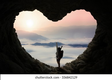 Silhouette of female backpacker with bag, standing inside cave shaped heart symbol while enjoying mountain view