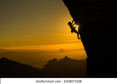 Silhouette of a female climber climbing a cliff during a beautiful orange sunset