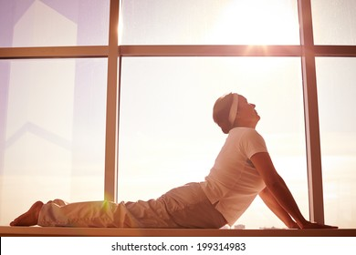 Silhouette of female doing physical exercise on background of window