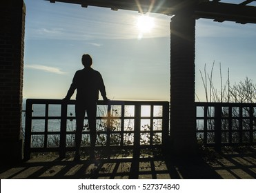 Silhouette female enjoying the sea view from a balcony in the sunlight - horizontal