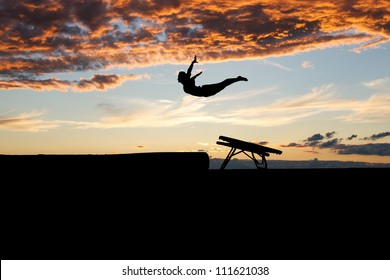 silhouette of female gymnast jumping on mini trampoline in sunset