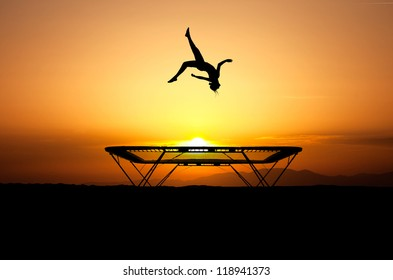 silhouette of female gymnast jumping on trampoline