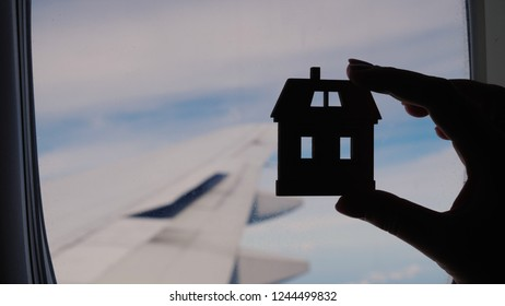 Silhouette of a female hand with a small house. Against the background of the plane's window. Concept - homesickness
