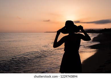Silhouette of female in a hat at sunrise on a beach.