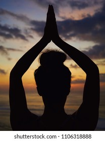 Silhouette of a female head and arms in namaste pose over her head in colorful sunset sky background