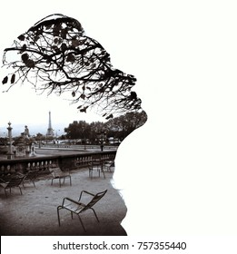 Silhouette of a female head (profile), framing fragment of Paris panorama with the Eiffel Tower in the background, double exposure. Black and white photo, bright background. Cold toning