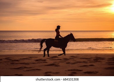 Silhouette of Female Horse Rider Cantering on the Sandy Beach at Sunset