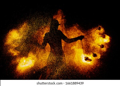 Silhouette of a female magician doing a fire show. Fire sparks fly around a woman. The magician is wearing a leather cloak and hat.