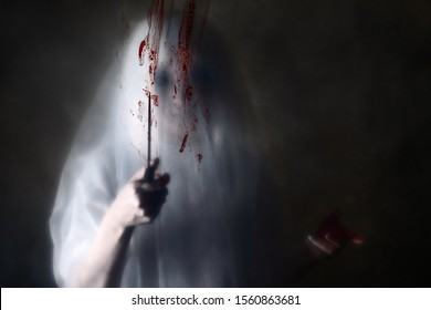 Silhouette of female maniac or killer or horror murderer with knife in hand in standing behind plastic film with blood. Criminal halloween robber or rapist concept in thriller atmosphere