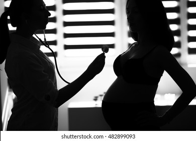 Silhouette female medicine doctor holding stethoscope to pregnant woman standing for encouragement, empathy, cheering,support, medical examination. New life of abortion concept. B/W style