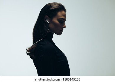 Silhouette of female model in studio. Side view of young woman wearing earphones on grey background.