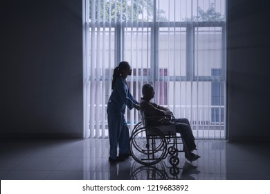 Silhouette of female nurse pushing her elderly patient in a wheelchair while walking near the window