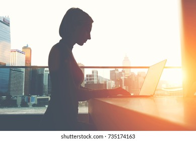 Silhouette of female person with hidden face hacker uses an Internet connection while maintaining anonymity. Hacking a computer. Woman searching information in network via laptop