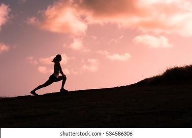 Silhouette of female runner doing leg stretches before her run.