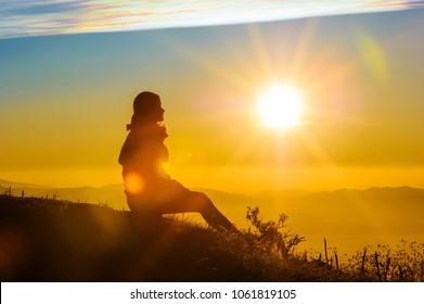 silhouette of female traveler looking a beautiful sunrise and mountains with blue sky  in the morning, chiang mai in thailand