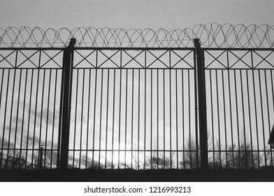 Silhouette of fence with barbed wire on film. Gloomy black and white overcast background with prison. Atmospheric scanned analog photography with grain and scratch. Lomography of private property.