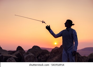 Silhouette of fencer man throwing up his fencing sword on a sunset background
