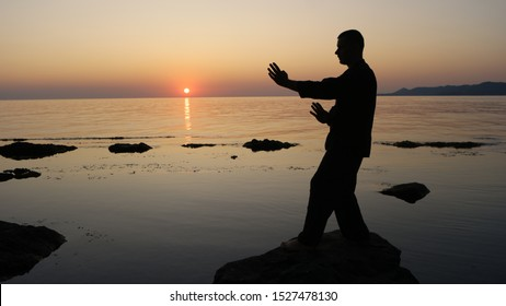 Silhouette of a fighter Wing Chun against the backdrop of sea sunset. fighting stance. Object location on the right