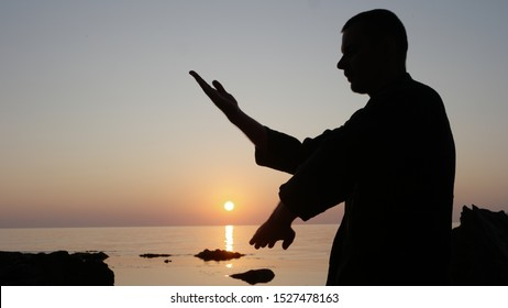 Silhouette of a fighter Wing Chun on a background of sea sunset. Kwun Sao Form close-up