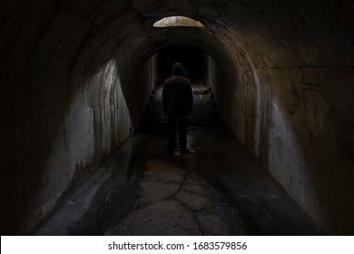 The silhouette of the figure of a man going into unknown darkness in a gloomy dark old underground passage lit by sunlight through a hatch in the ceiling.