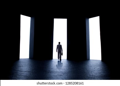 silhouette figure of a young man in a business suit with a briefcase in front of three open doors with light, person decides what path to choose, the concept of life choices and business