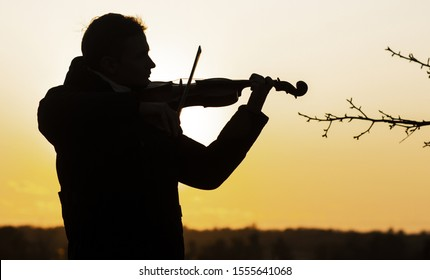 silhouette figure of a young violinist in a jacket at sunset, a man playing the violin in nature, music and art concept