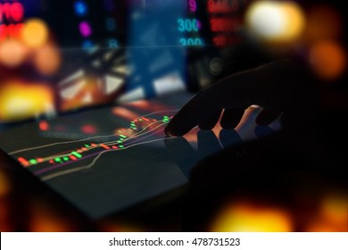 Silhouette finger on tablet with technical graph trading screen with abstract blur smartphone bokeh background , stock market concept