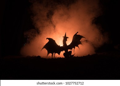 Silhouette of fire breathing dragon with big wings on a dark orange background. Selective focus
