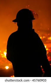 The silhouette of Fire Fighter watching a fire