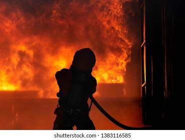 Silhouette firefighter in a  Extinguish Orange suit using extin