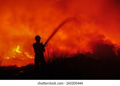Silhouette of fireman fighting bushfire at night.
