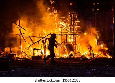 Silhouette of fireman trying to control a fire in a street during a night.