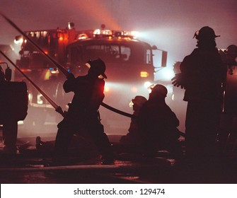 Silhouette of firemen and fire truck.