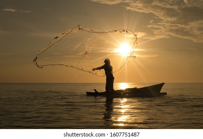 silhouette of fisherman in action during net casting. selective focus. business concept.