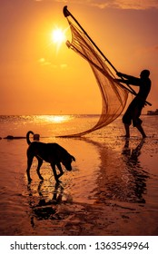 Silhouette of fisherman & adorable doggie with vibrant orange sky background