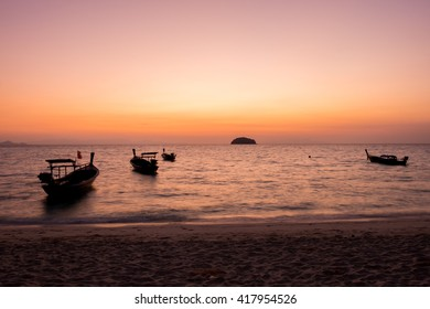 Silhouette of fisherman boat floating in the sea on dramatic sunset and sunrise sky.