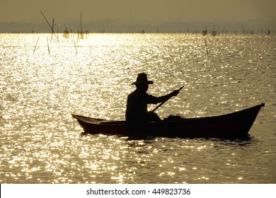 Silhouette fisherman with boat in golden lake reflective lighting on sunrise time,select focus with shallow depth of field