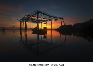 Silhouette of fisherman boat hut at a beach with beautiful sky reflection during sunrise (soft focus, shallow DOF, slight motion blur)