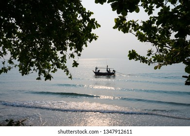 Silhouette of Fisherman boat on the sea with tree branch