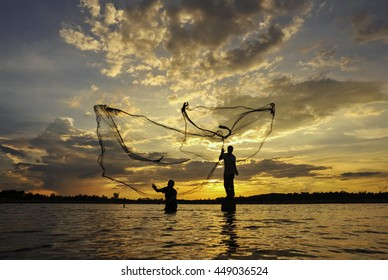 Silhouette  fisherman casting a nets into the water during sunset