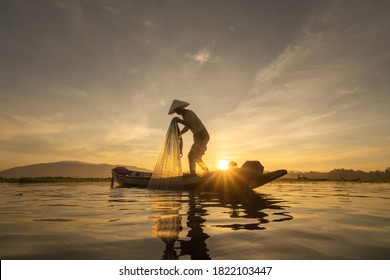Silhouette Fisherman casting or throwing a net for catching freshwater fish in nature lake or river with reflection in morning time in Asia in Thailand. People.