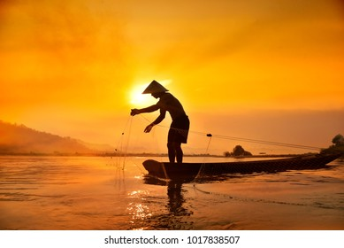 Silhouette of Fisherman catching fish in lake by using fishing net at beautiful