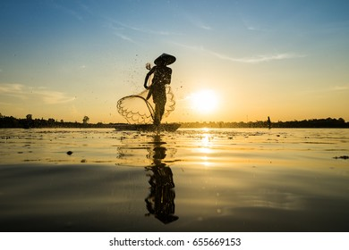 Silhouette of Fisherman catching fish in lake by using fishing net at beautiful sunset time.