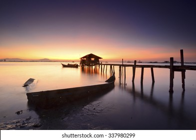 Silhouette of fisherman cottage during sunrise.