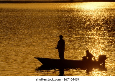 Silhouette Of Fisherman during sunrise in Kenyir Lake, Malaysia
