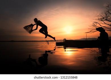 Silhouette Fisherman Family and amazing sunrise Bang Phra Reservoir Chonburi Province Thailand.