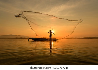 Silhouette Fisherman Fishing Nets on the boat,Thailand.