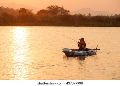 Silhouette of fisherman fishing on kayak on reservoir in Thailand.