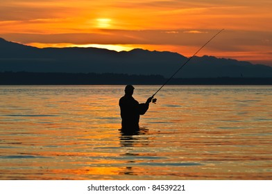 Silhouette of a fisherman with a fishing pole at sunset.